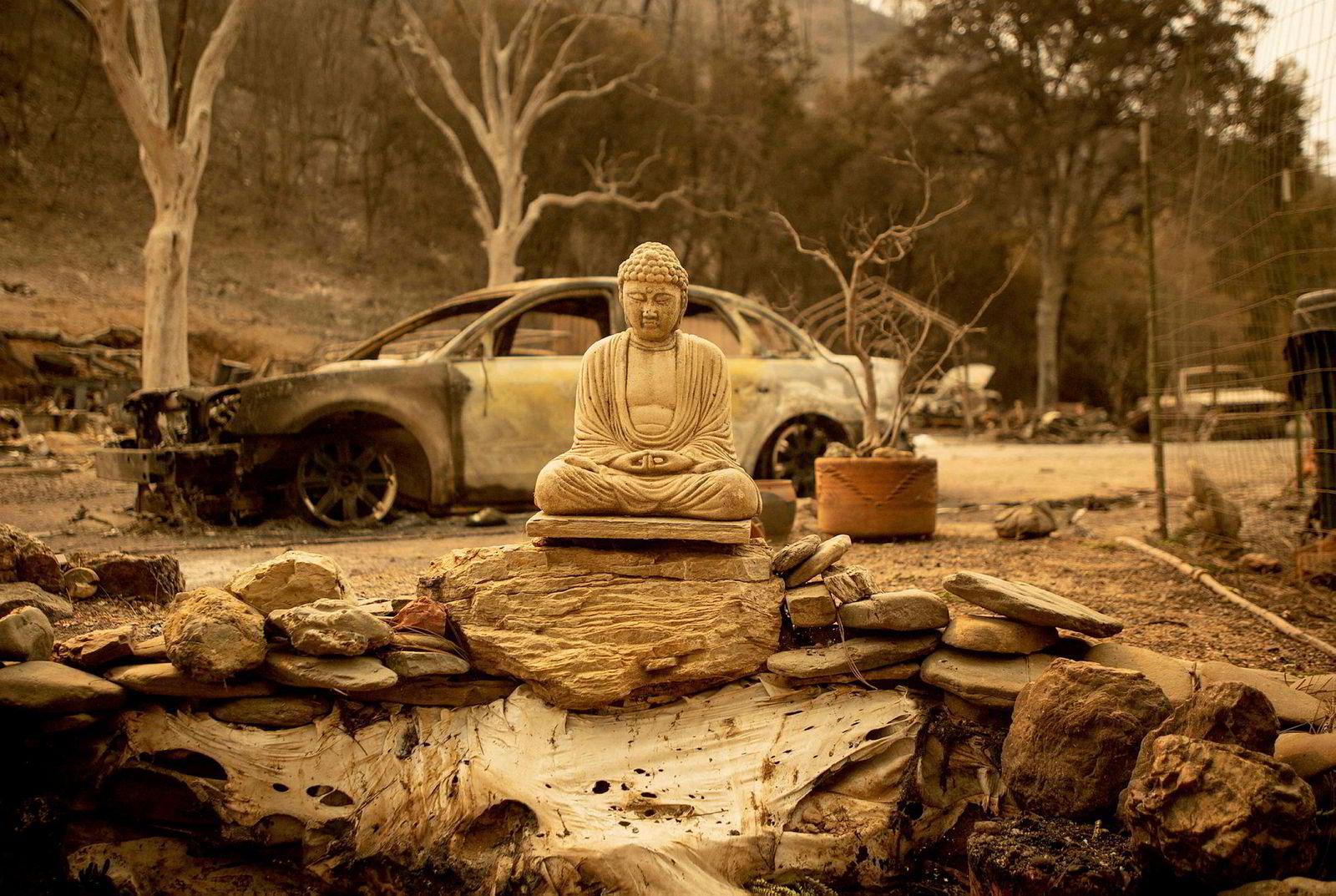 En Buddha-statue står igjen blant restene av et nedbrent hjem i Spring Valley.