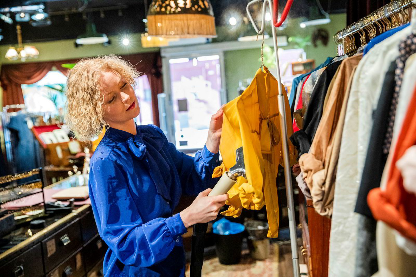 Karoline Gullberg gjør klar bluser for fotografering, de jobber for å få solgt mest mulig på nett når kundene uteblir i butikken.