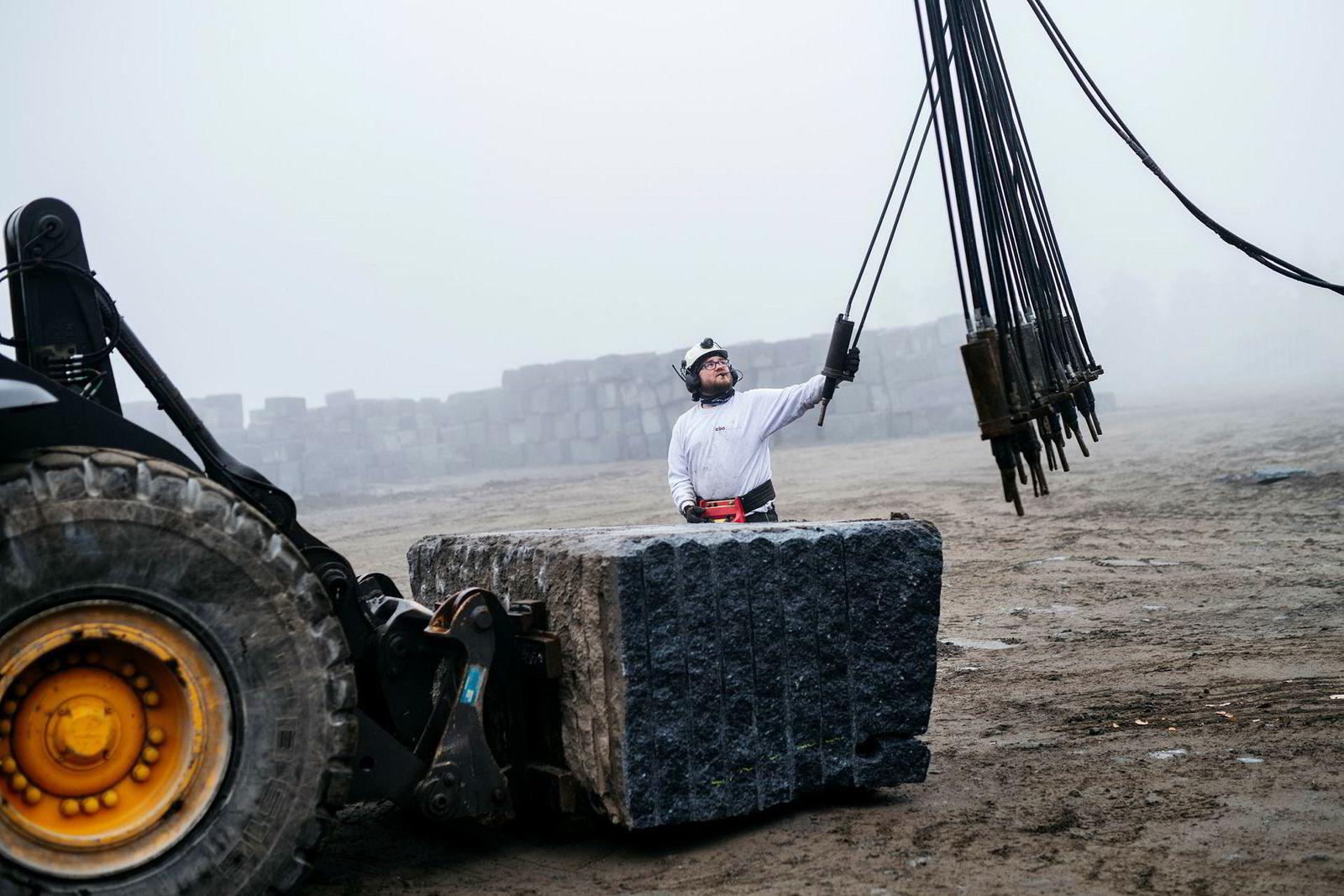 Andreas Bjørgan forbereder kiling av en granittblokk. Steinblokkene grovdeles ved hjelp av bor og kiling, før Mjølner biter seg gjennom steinblokkene for å gi en naturlig røff knekkflate.