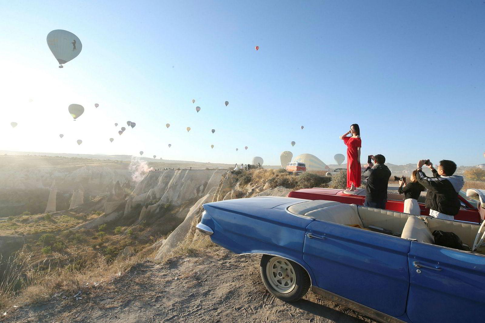 Turister tar bilder mens varmluftsballonger glir over Goreme-distriktet i den historiske Cappadocia-regionen i Tyrkia 30. september 2019. Cappadocia er bevart som et UNESCOs verdensarvsted og er kjent for sine skorsteinsbergarter, varmluftsballongturer, underjordiske byer og boutiquehoteller skåret ut i steiner.