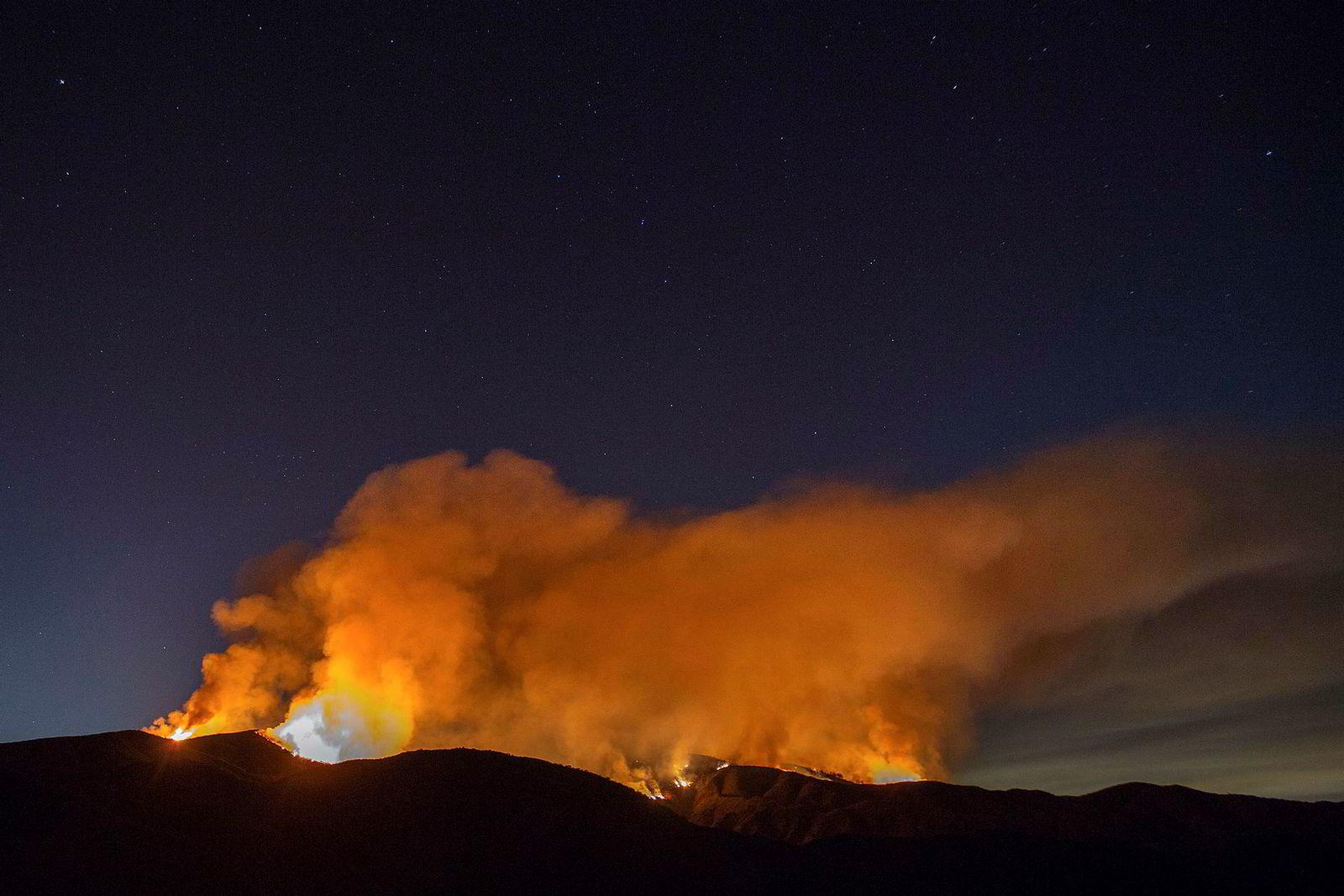 Karlsvogna skimtes i bakgrunnen av en brennende fjellside nær Elsinore-innsjøen i California.