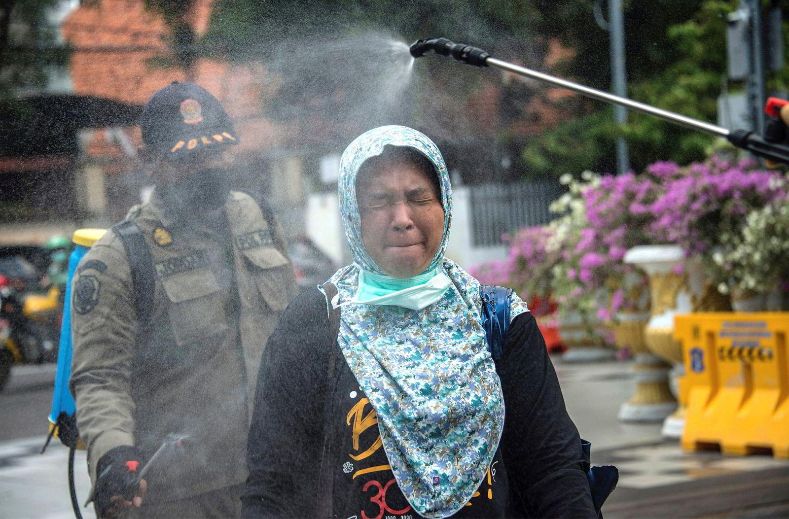 En kvinne sprayes med desinfiserende middel før hun slipper inn på et offentlig kontor i Surabaya i Indonesia. Sprayingen er et føre var-tiltak mot koronaviruset.