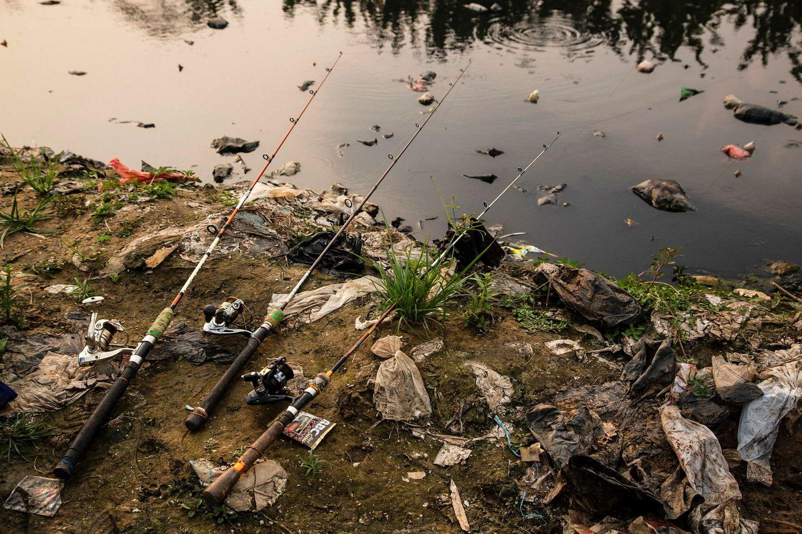 En lokal fisker har satt ut tre fiskestenger i håp om å få et måltid ut av den sterkt forurensede Citarum-elven.
