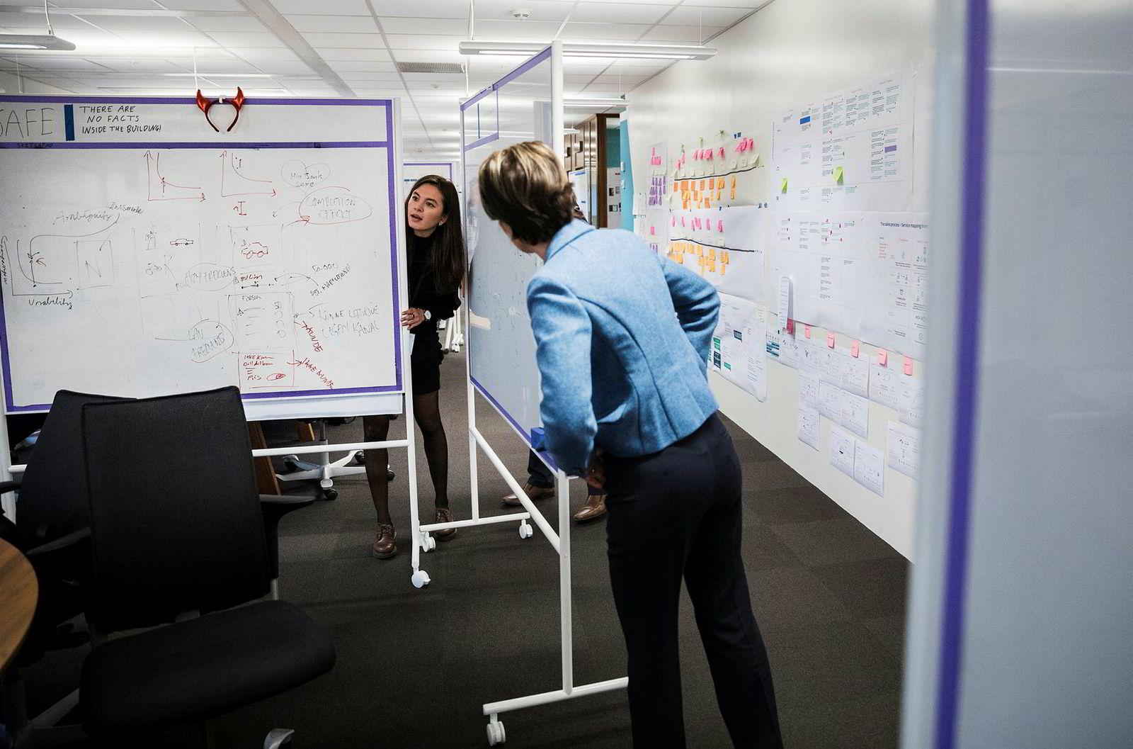 Negina Mamadova (til venstre) viser direktør Liv Fiksdahl et prosjekt hun jobber med på DNBs «Digital floor».