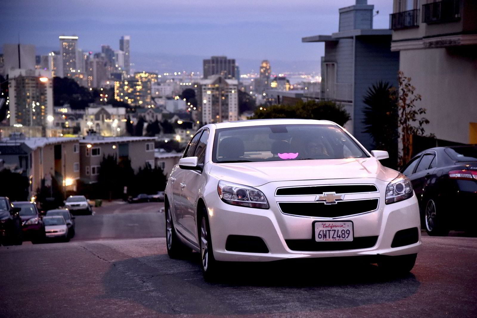En Lyft-sjåfør, med den karakteristiske logoen på frontvinduet, venter på en kunde i San Francisco.