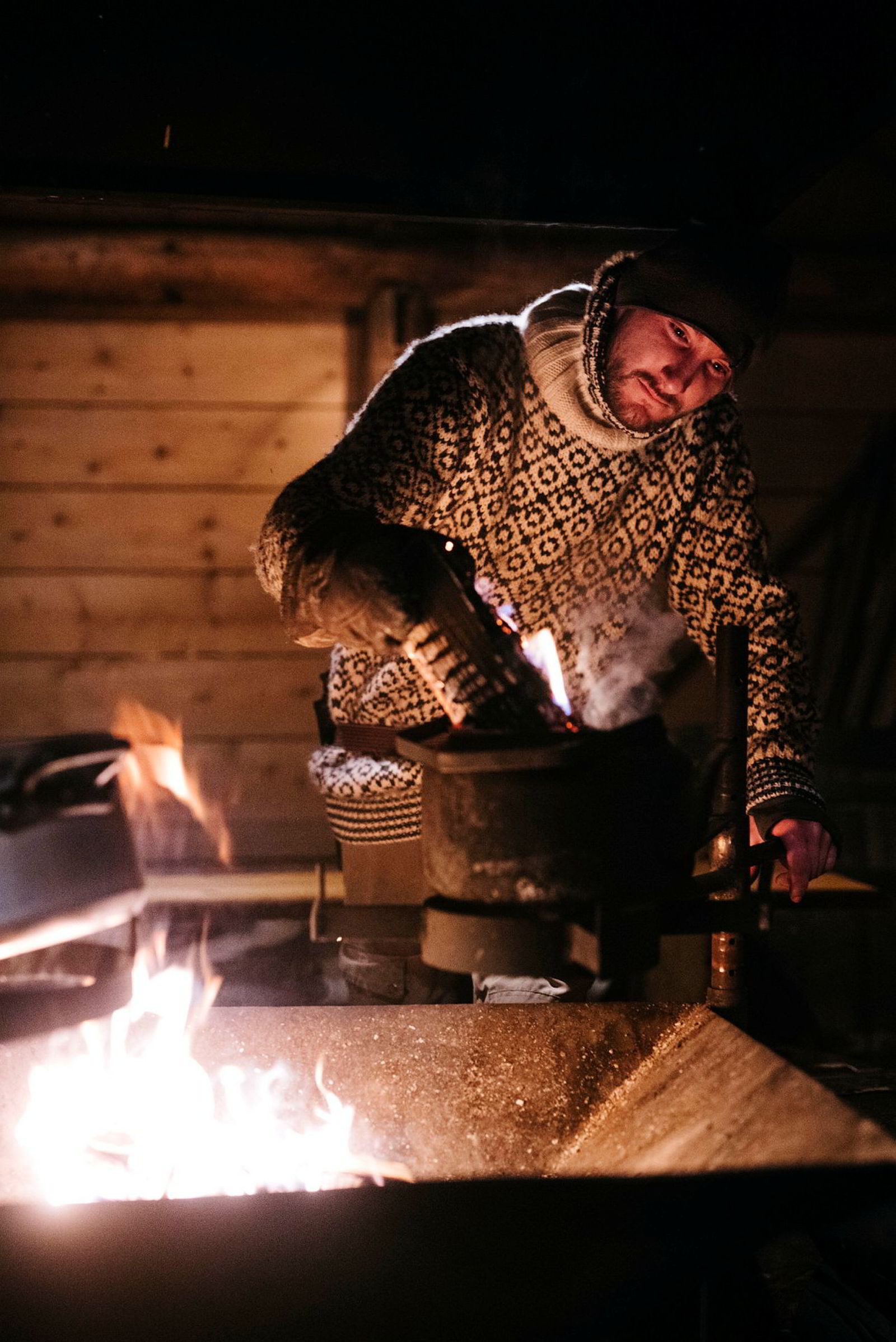 Guide og driftsleder ved Camp Barentz Alexander Hovland lager «Svalbardkaffe». Å røre med en glødende vedkubbe skal angivelig gi en interessant røyksmak.