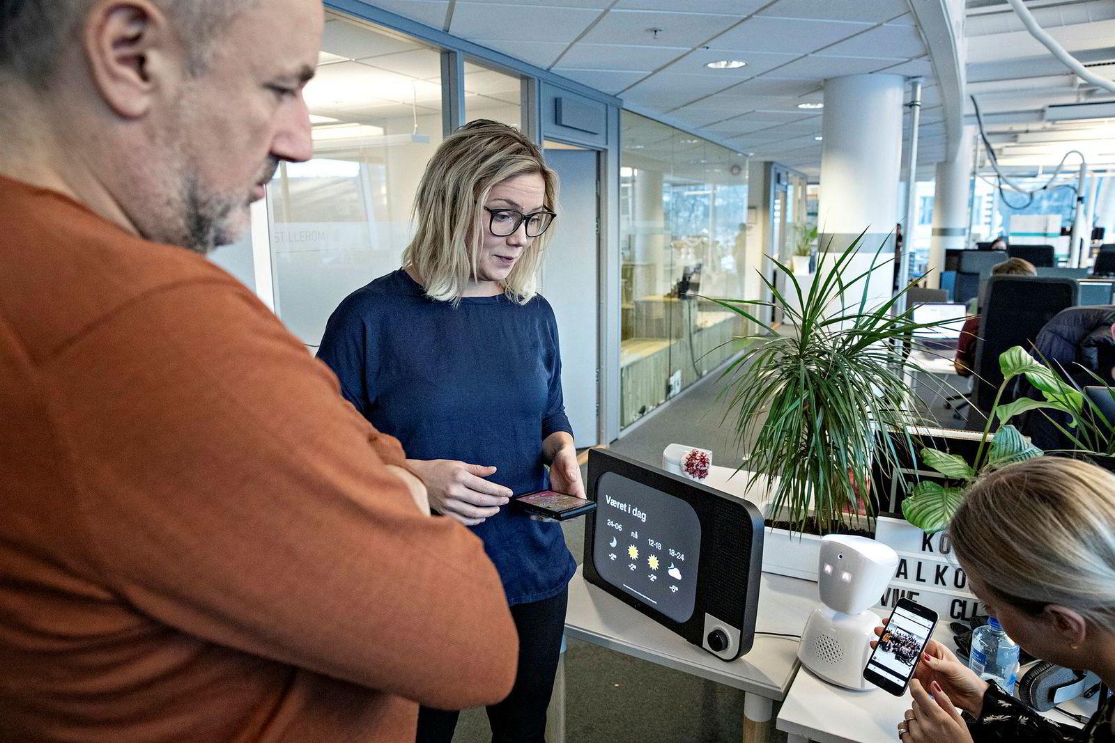 Oda Benedicte Løkholm Lewin viser Espen Agdestein fra fondet Idekapital og No Isolation-sjef Karen Dolva (midten) hvordan familiemedlemmer kan bruke en app til å sende bilder og meldinger til Komp-skjermen (med svart ramme).