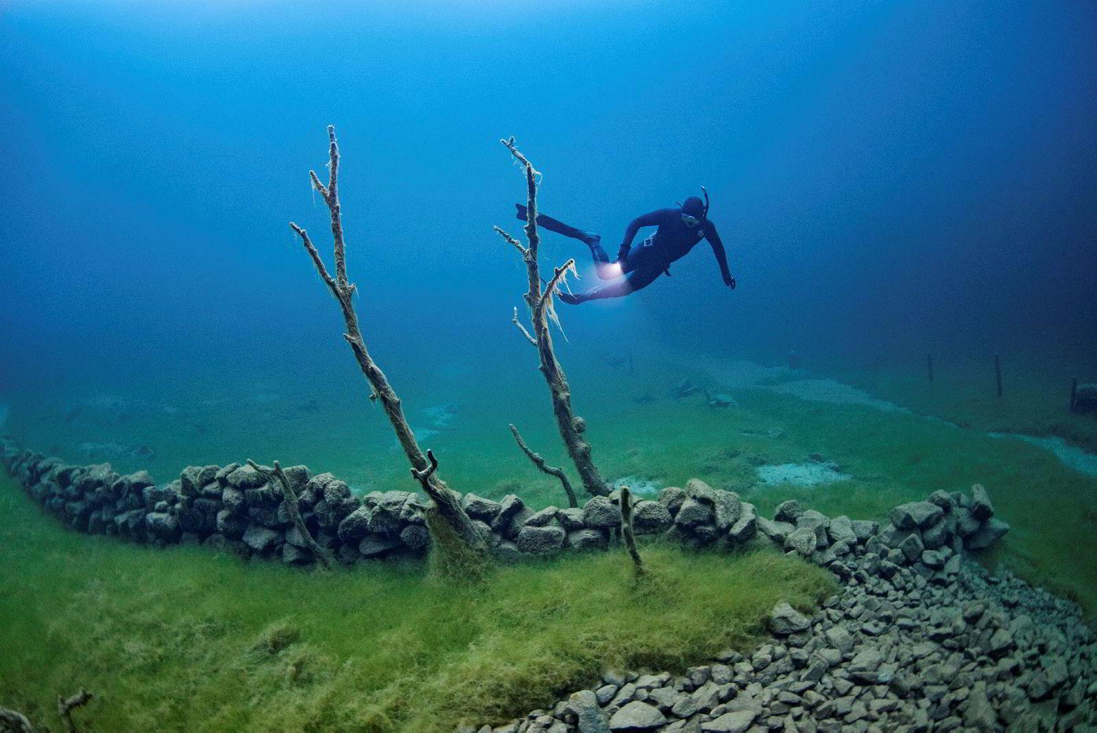 Et ras i 1908 demmet opp endel av Norangsdalen og skapte Lyngstøylsvatnet. Stian Kavli svømmer blant restene av gamle gårder og støler.
