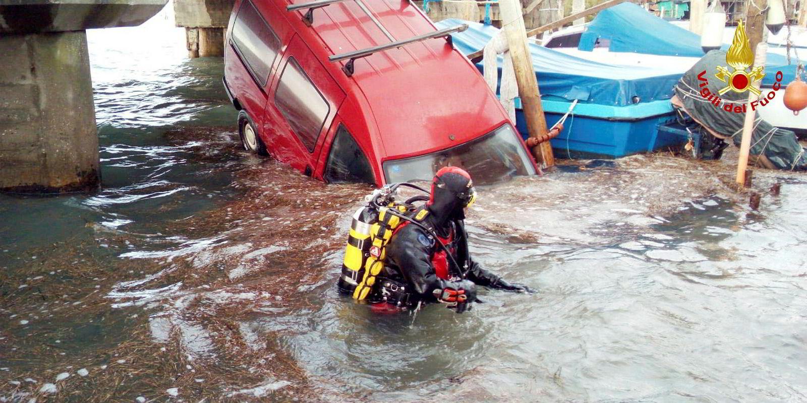 En brannmann i dykkerutstyr leter i vannet rundt en druknet bil