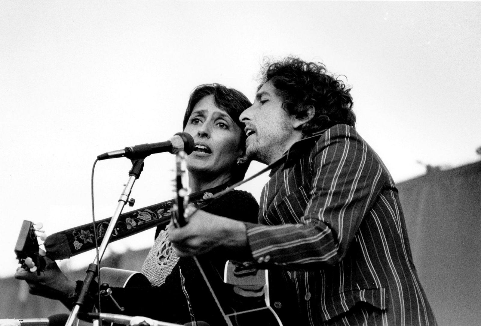 Den politiske musikkens tungvektere, Joan Baez og Bob Dylan opptrer sammen foran 80.000 tilskuere på et atomnedrustningsmøte på Rose Bowl i Pasadena, Calfornia i 1982. Baez og Dylan er helt sentrale på denne topplisten. Baez er den som er mest knyttet til vinneren «We Shall Overcome» og Dylan har intet mindre enn tre sanger blant de tolv første på listen.
