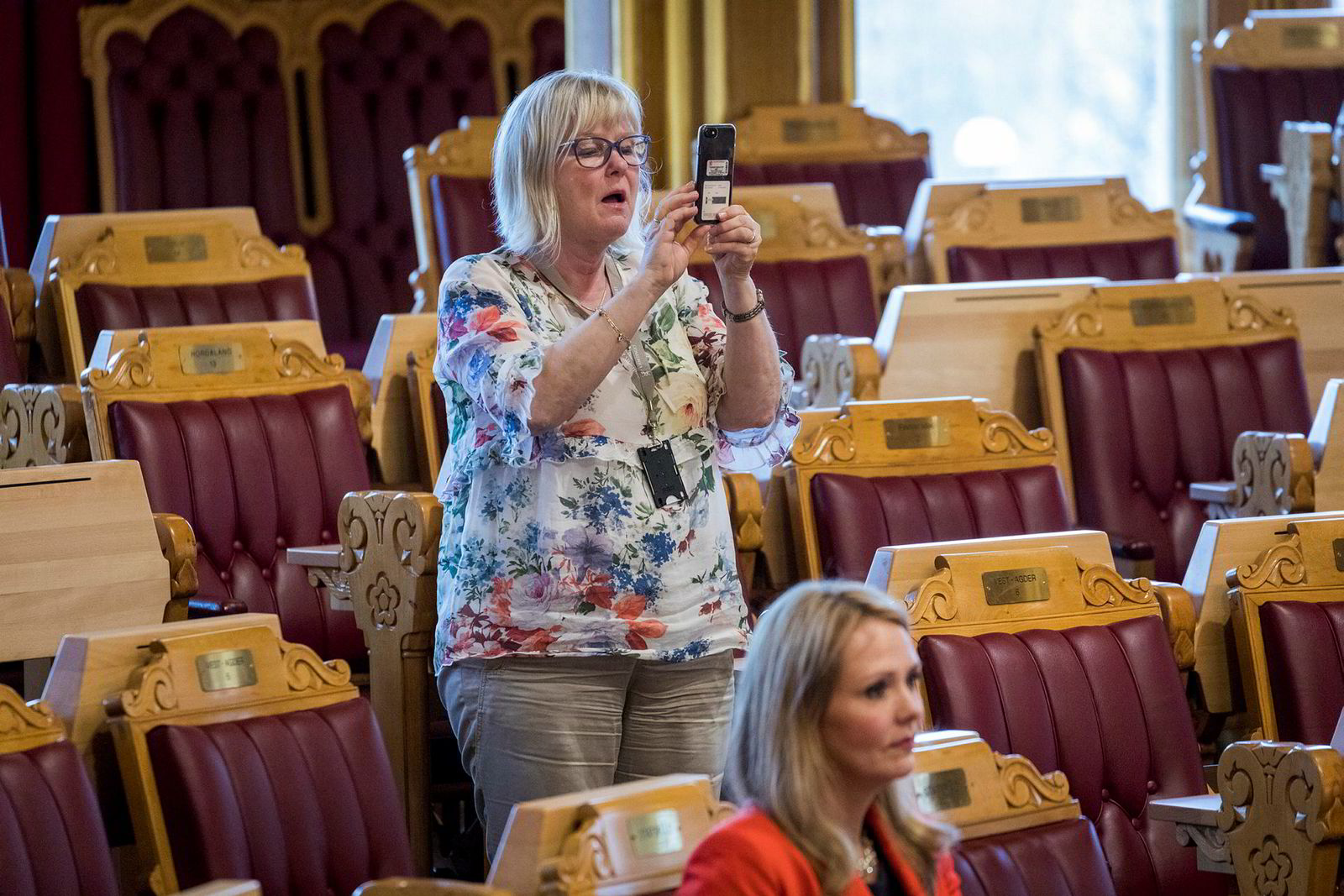 Ingalill Olsen (Ap) fotograferer med mobilen under spontanspørretimen. I forgrunnen tidligere barne- og likestillingsminister Linda Hofstad Helleland.