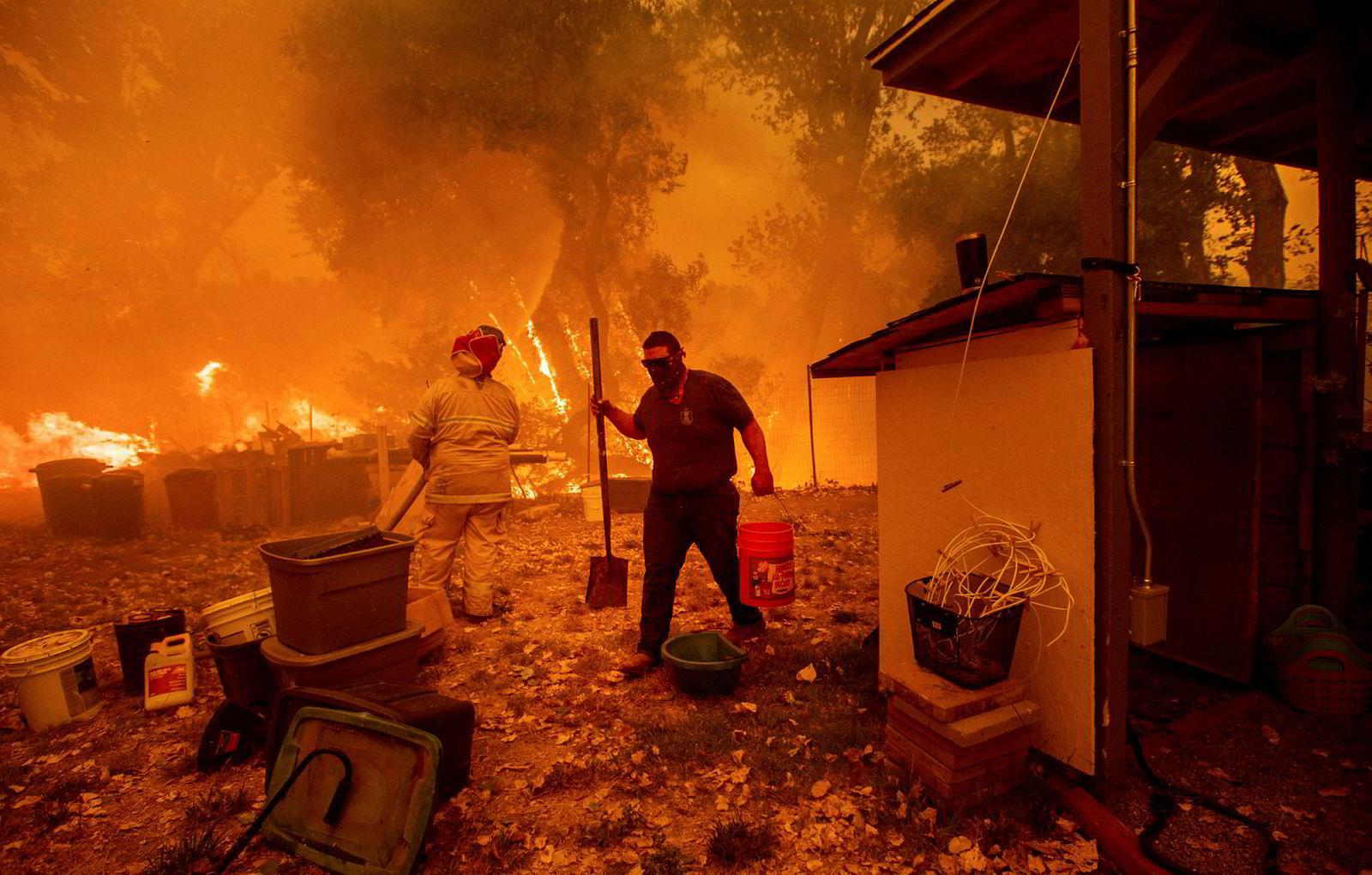 Lane Lawder forsøker å redde hjemmet sitt fra flammene nær Clearlake Oaks. Brannene har ødelagt flere hundre bygninger og drevet titusener fra hjemmene sine.