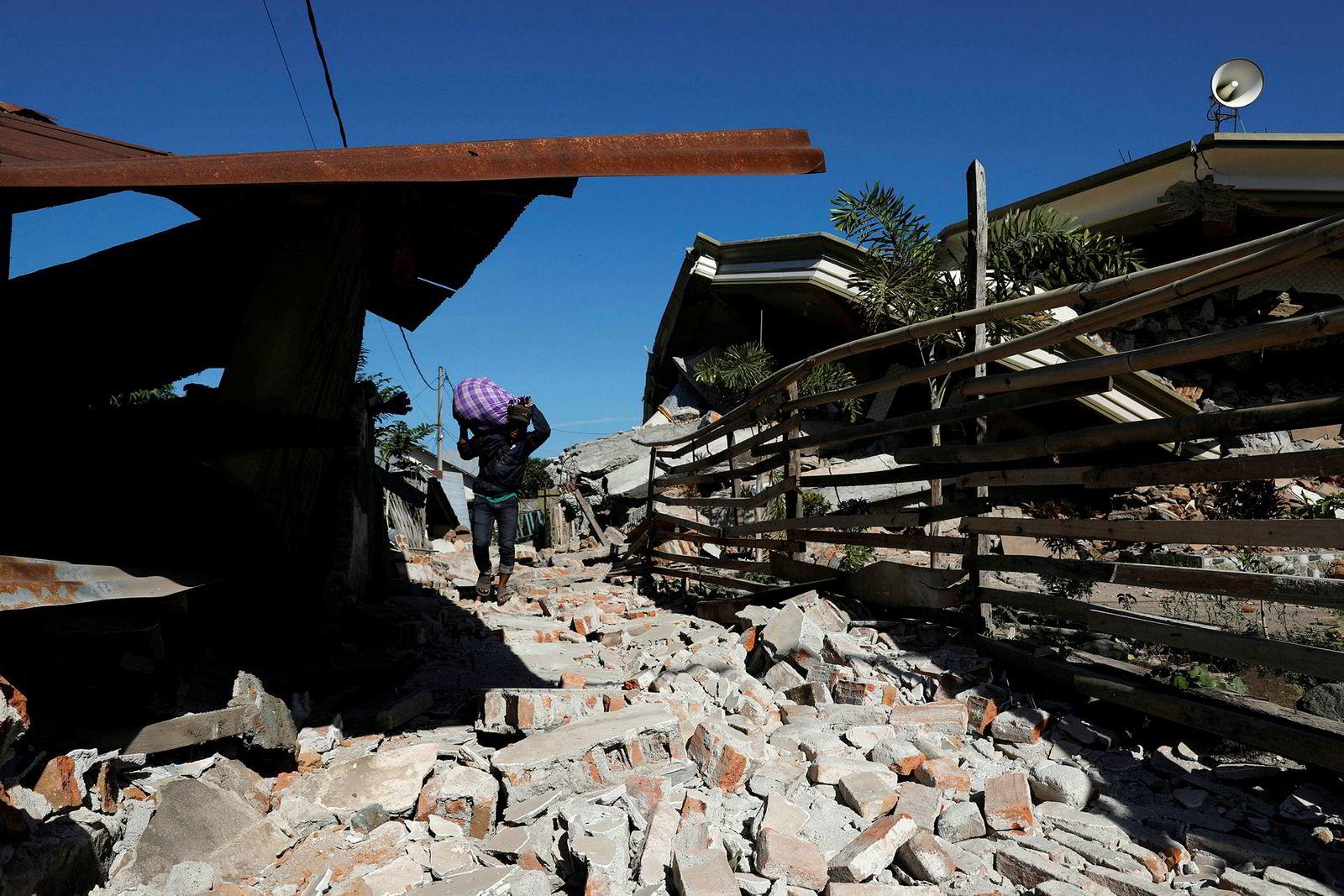 En mann bærer eiendelene sine gjennom ruinene av en moské etter jordskjelvet som rammet øya Lombok i Indonesia.