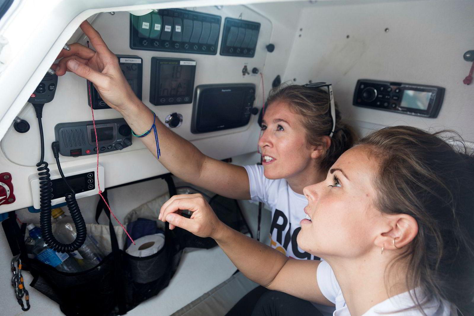 Cornelia Bull, til venstre, og Hege Svendsberget går gjennom de tekniske installasjonene i akterkabinen på robåten de skal bruke over atlanteren.
