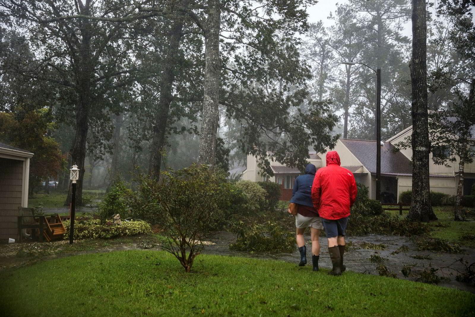 Ginger Thomas og Brett Harp går for å se på skadene på huset sitt i River Bend.