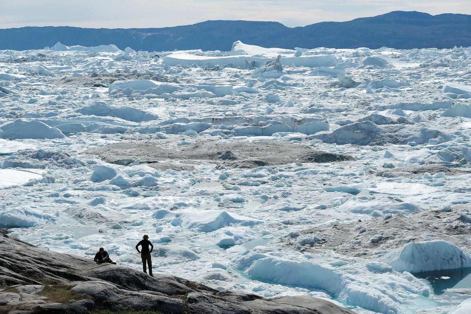 Turister ser på isen som flyter i Isfjorden ved Ilulissat på Grønland. Hetebølgen som noen dager tidligere sendte temperaturer til rekordnivåer i deler av Europa, traff Grønland de siste dagen i juli. Klimaendringene har en betydelig effekt på Grønland, der somrene er blitt lengre og isbreene trekker seg tilbake med stadig større hastighet.