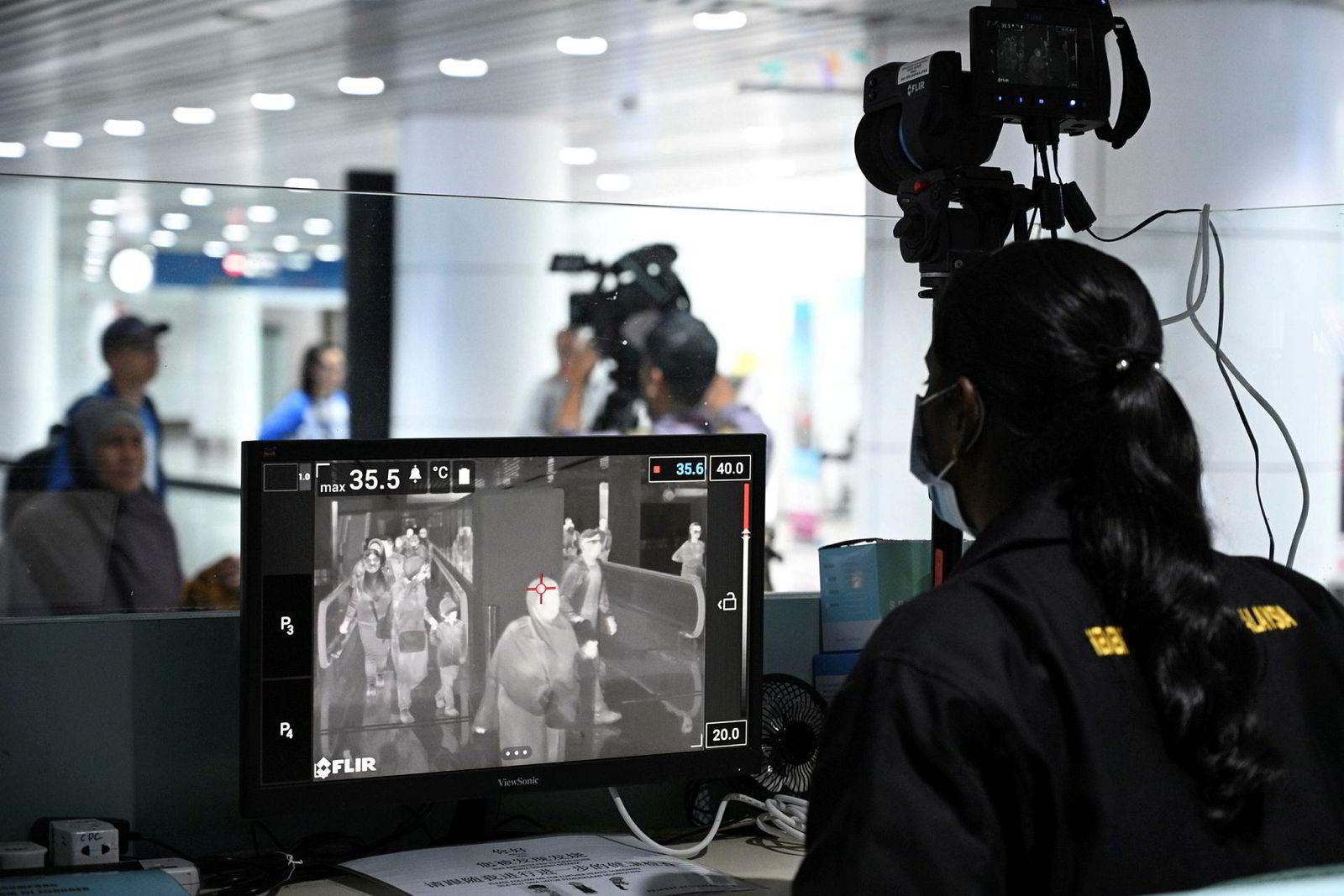 Helsepersonell på flyplassen i Malaysia skanner passasjerer som ankommer Kuala Lumpur International Airportfor å oppdage folk som har med seg det nye viruset.