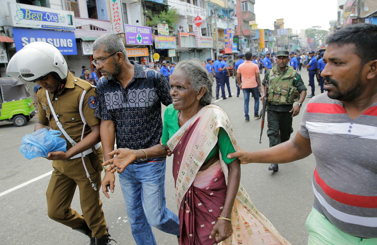 En eldre kvinne får hjelp nær St. Anthony's Shrine i Colombo.
