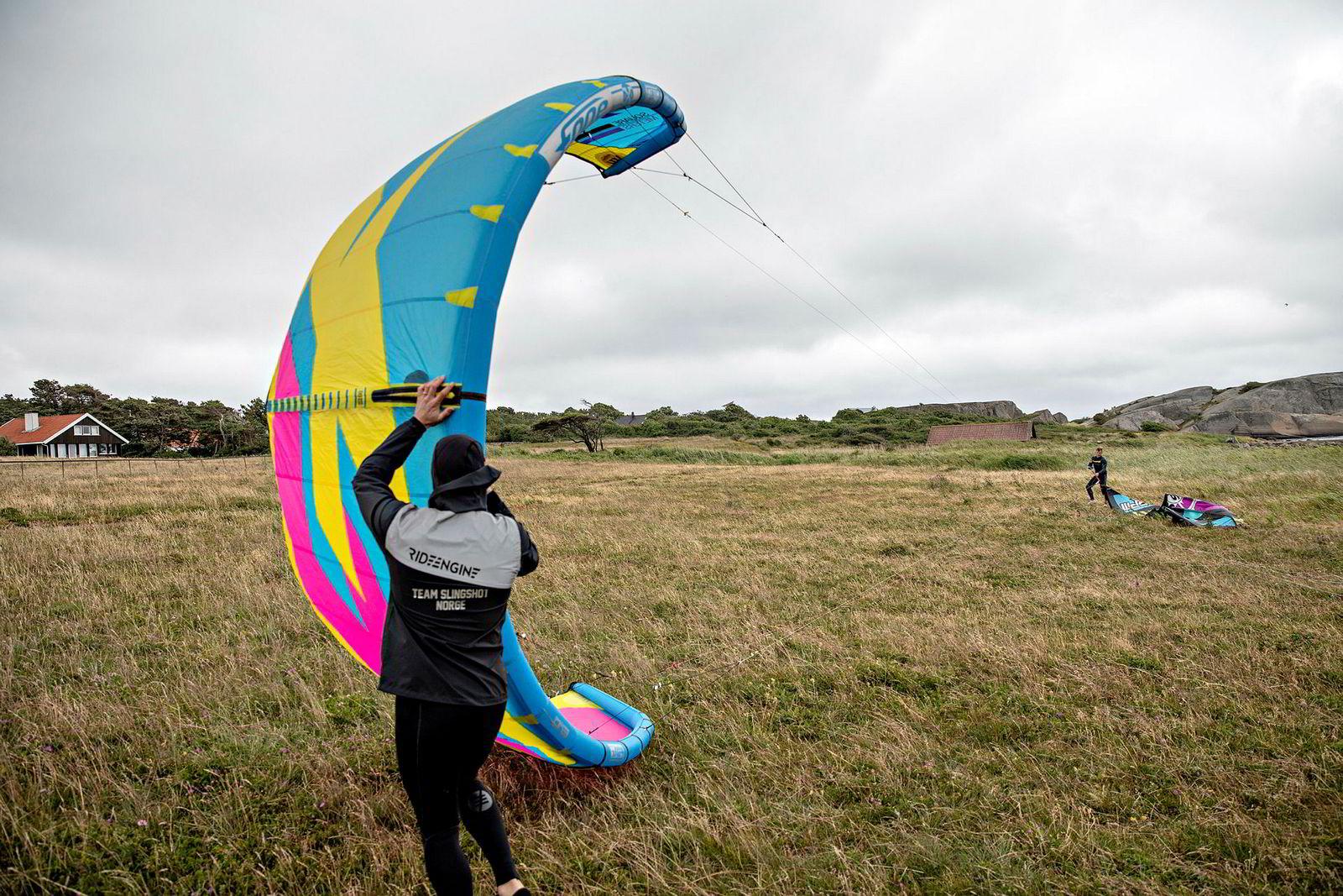 Blaze Coles hjelper Rakfjord med å få opp kiten på gressletten før utstyret tas med ut i vannet.