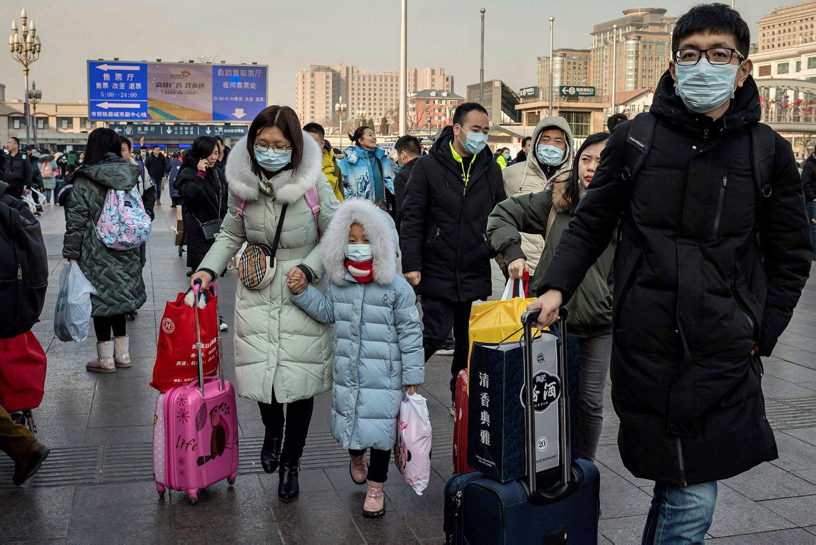 Folk i Beijing beskytter seg med ansiktsmasker. Det hittil ukjente coronaviruset er bekreftet å smitte mellom mennesker.