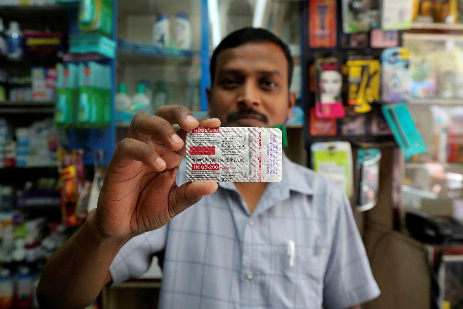 En apoteker i Mumbai i India viser frem malariamedisin laget av hydroxyklorokin.
