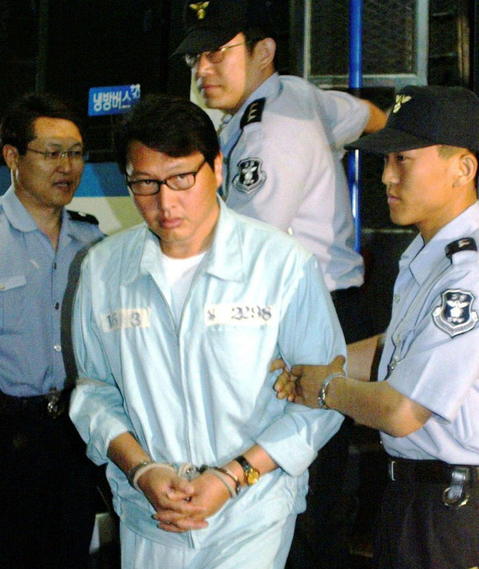 Chey Tae-won blir ført inn i en rettssal i Seoul i 2003 etter å ha blitt tiltalt for innsidehandel.