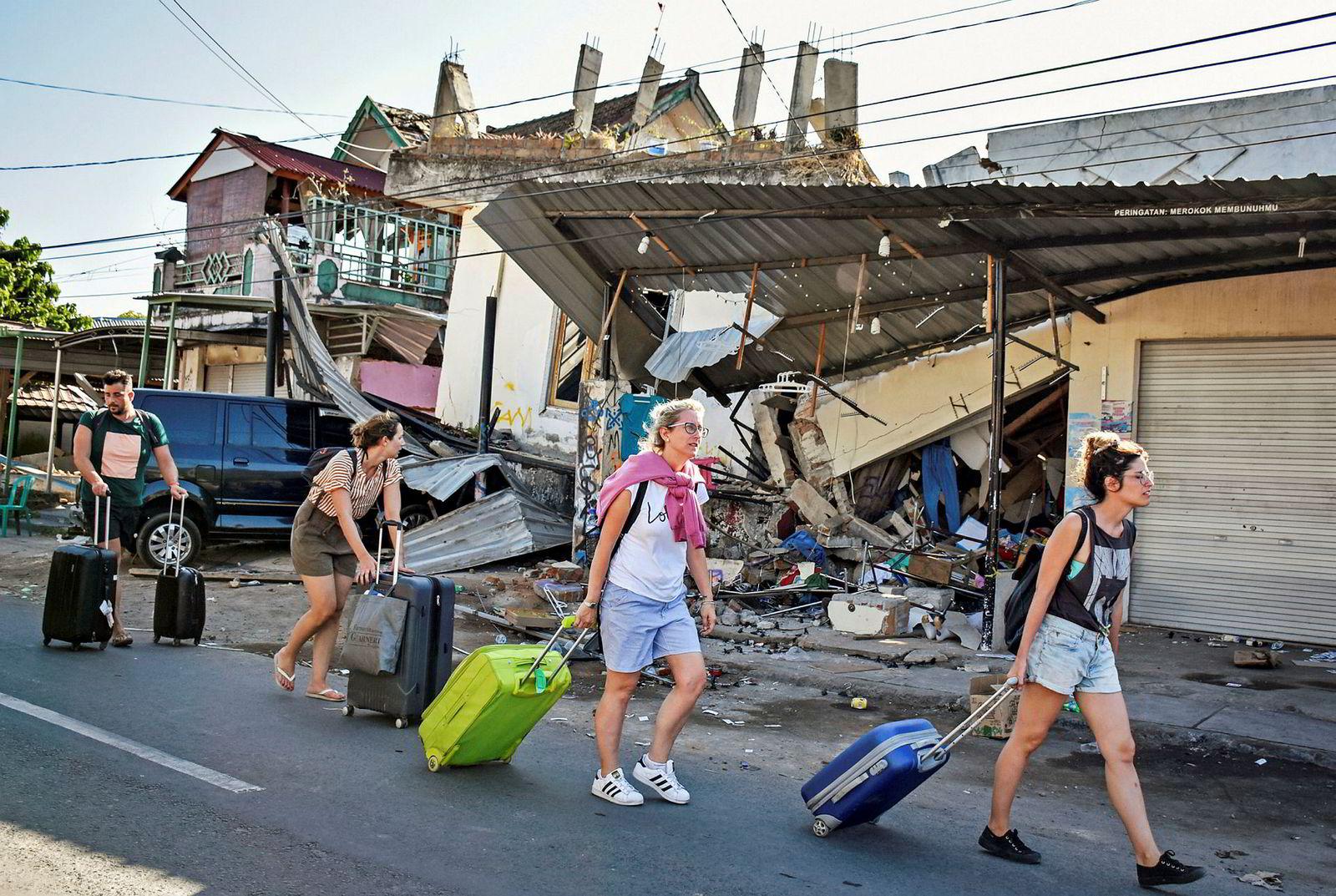 Utenlandske turister passerer raserte bygninger etter jordskjelvet i Pemenang på Lombok. Nesten 160.000 mennesker er blitt hjemløse som følge av søndagens skjelv, og tusenvis av turister har forlatt Lombok og naboøyene de siste dagene av frykt for nye skjelv.
