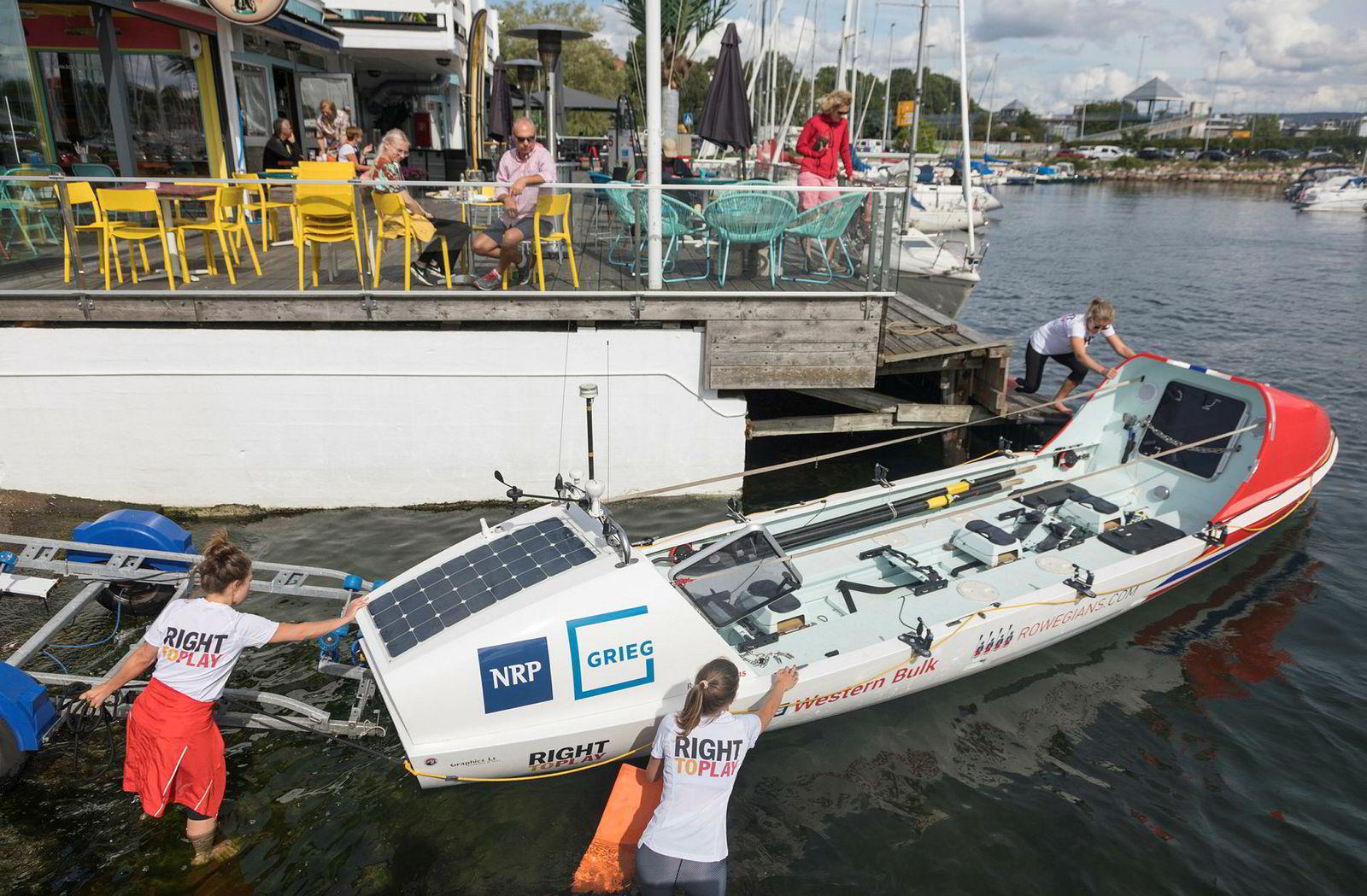 Rowegians sjøsetter sin nyfolierte robåt ved Kongen Marina med mange nysgjerrige blikk