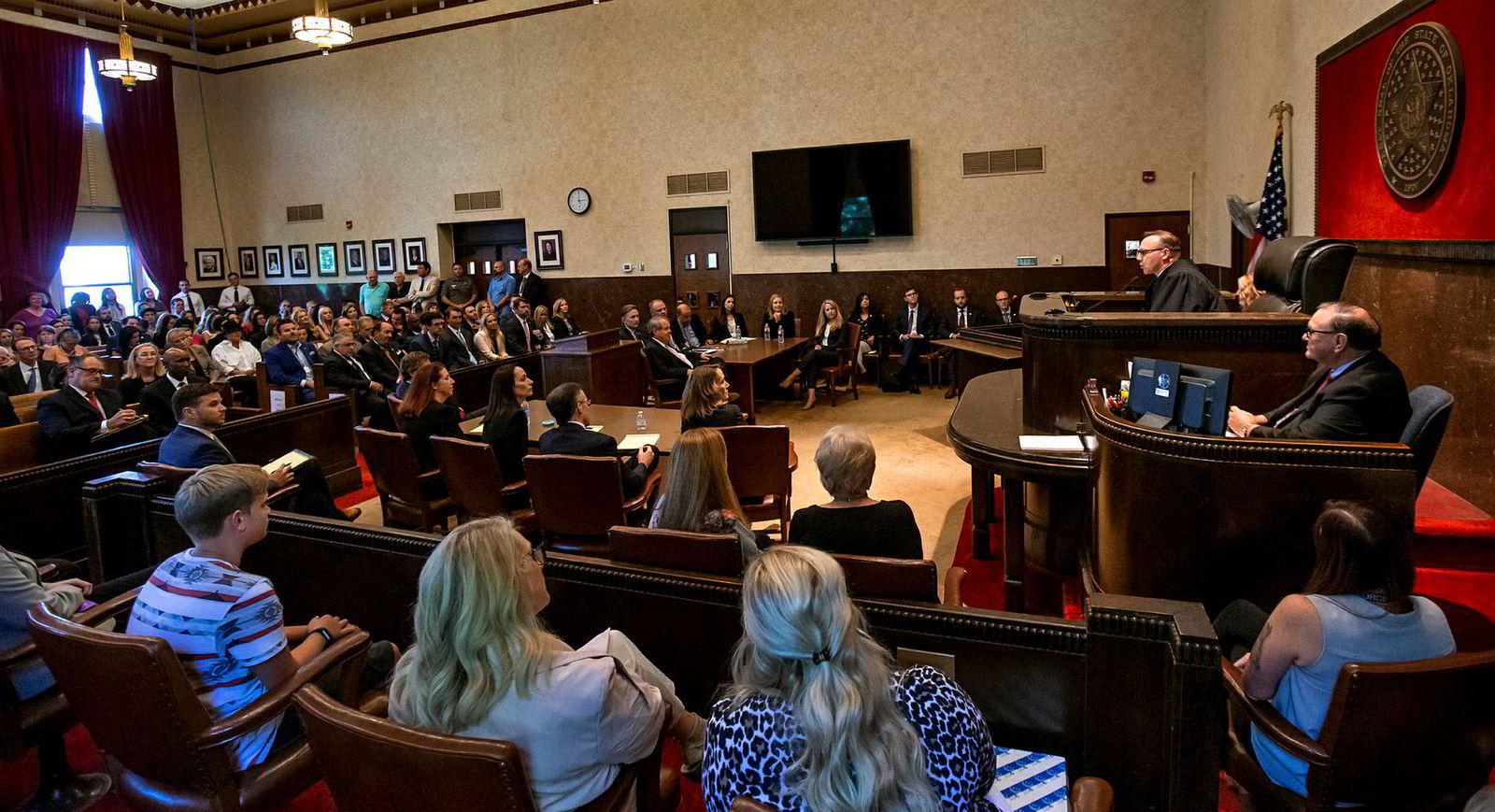 Dommer Thad Balkman i domstolen i Norman, Oklahoma, leser opp dommen mot Johnson&Johnson mandag. Blant tilhørerne var flere av opiodkrisens mange etterlatte og pårørende.