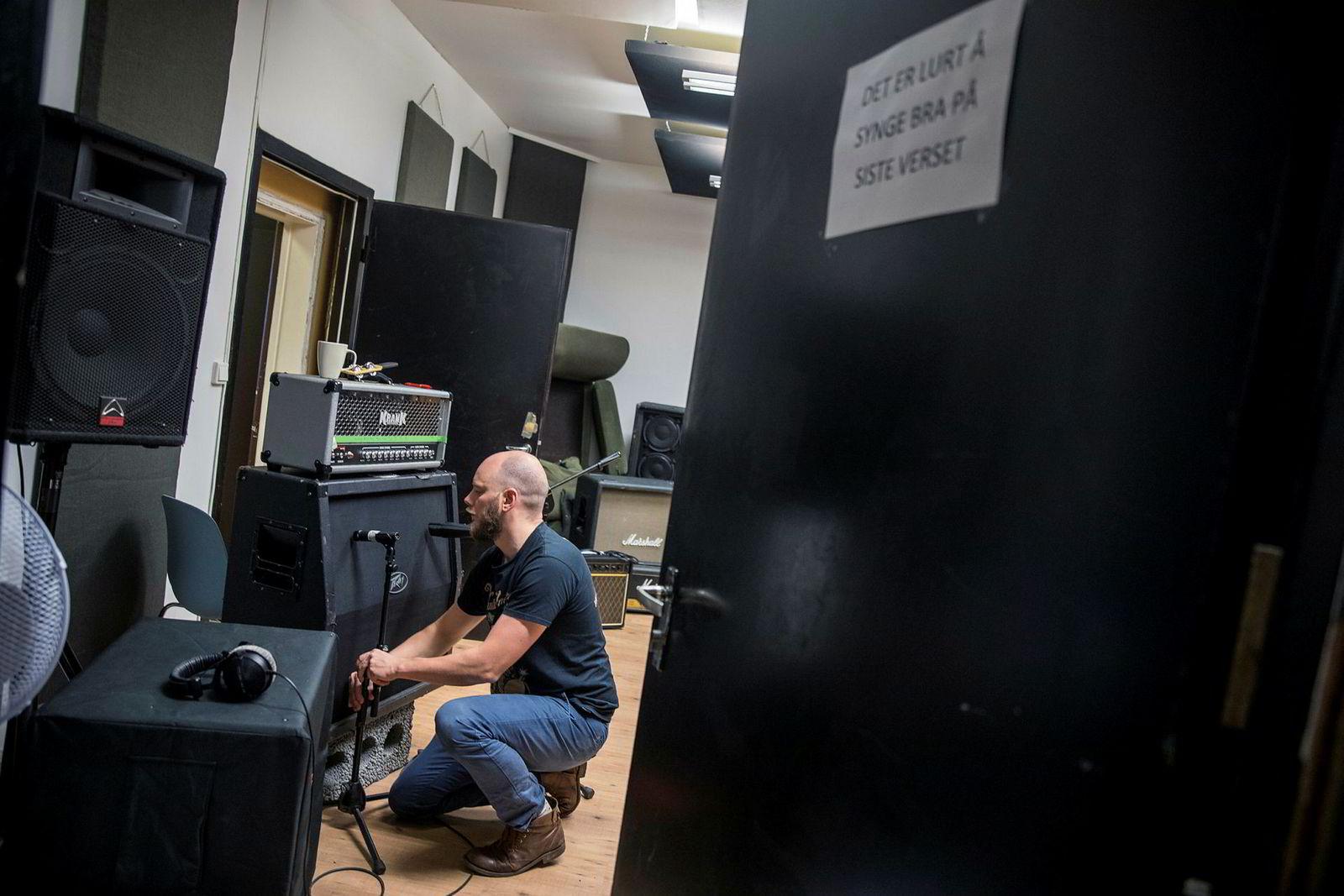 Daglig leder Bjørnar Erevik Nilsen mikker opp en høyttaler i det tilhørende platestudioet. En lapp på døren minner om at det er lurt å synge bra på siste verset.