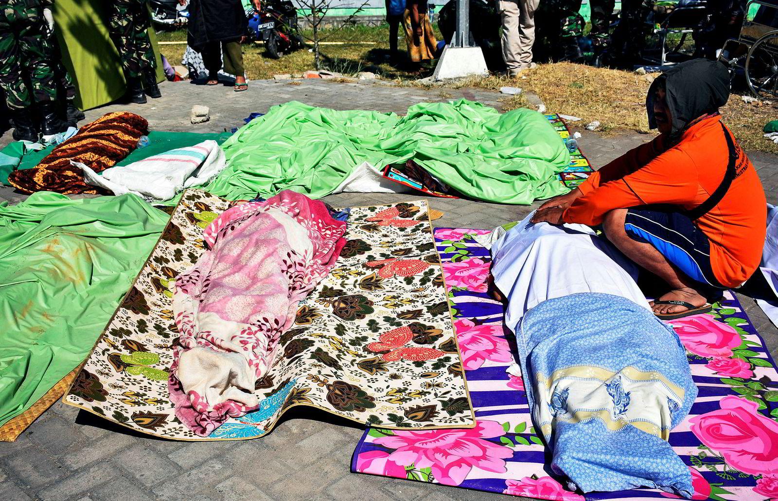 En mann sitter ved siden av liket til et familiemedlem som døde i et av jordskjelvene som har rammet Indonesia denne uken.