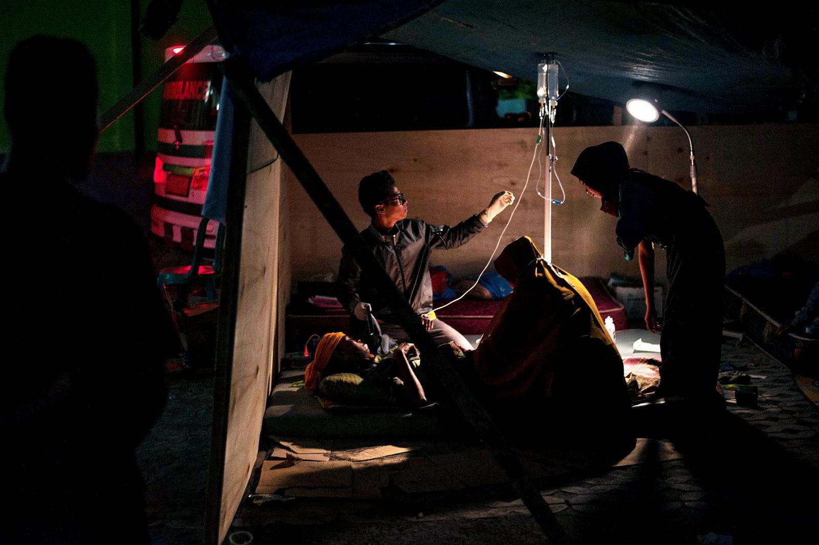En lege pleier et jordskjelvoffer på et midlertidig sykehus satt opp på Lombok-øya.