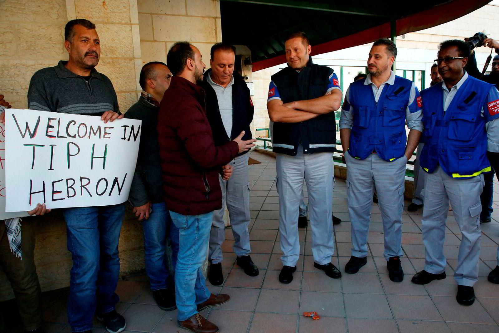 Observatører fra TIPH, her sammen med lokale palestinere, foran hovedkvarteret i Hebron. Nå må de forlate området.