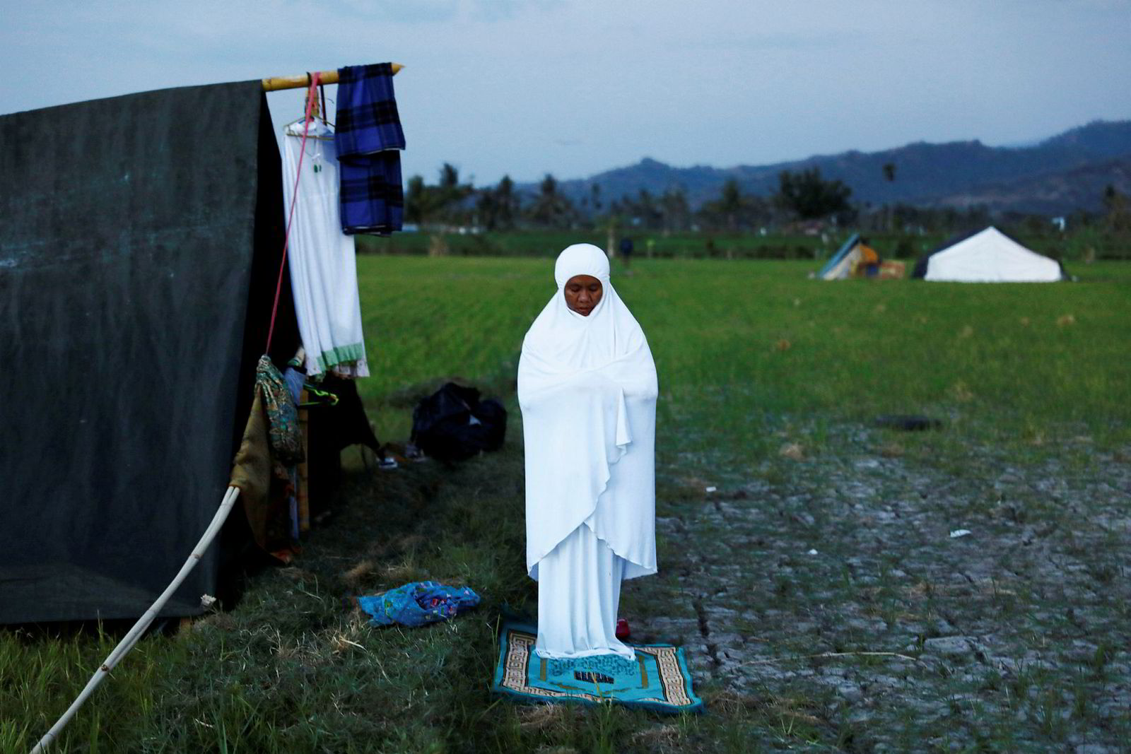 En kvinne ber nær teltet hun har fått tildelt av redningsmannskap på øya Lombok etter søndagens jordskjelv.