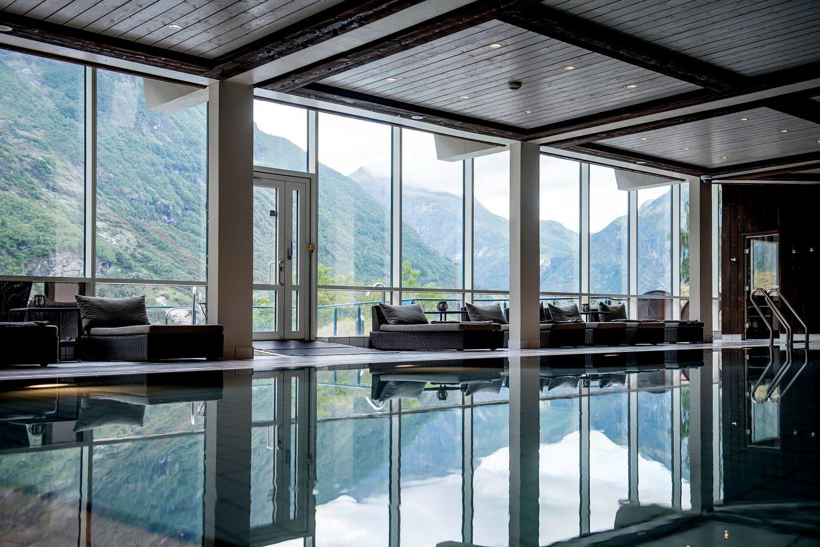 Innendørsbasseng med direkte tilknytning til en terrasse med utsikt over Geirangerfjorden.