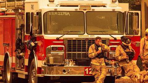 Slitne brannmannskaper tar en hvil i nærheten av Santa Rosa i California.