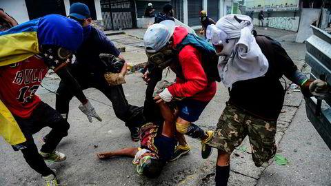 Opposisjonelle demonstranter forsøker å hjelpe en skadet venn etter sammenstøt med politiet.