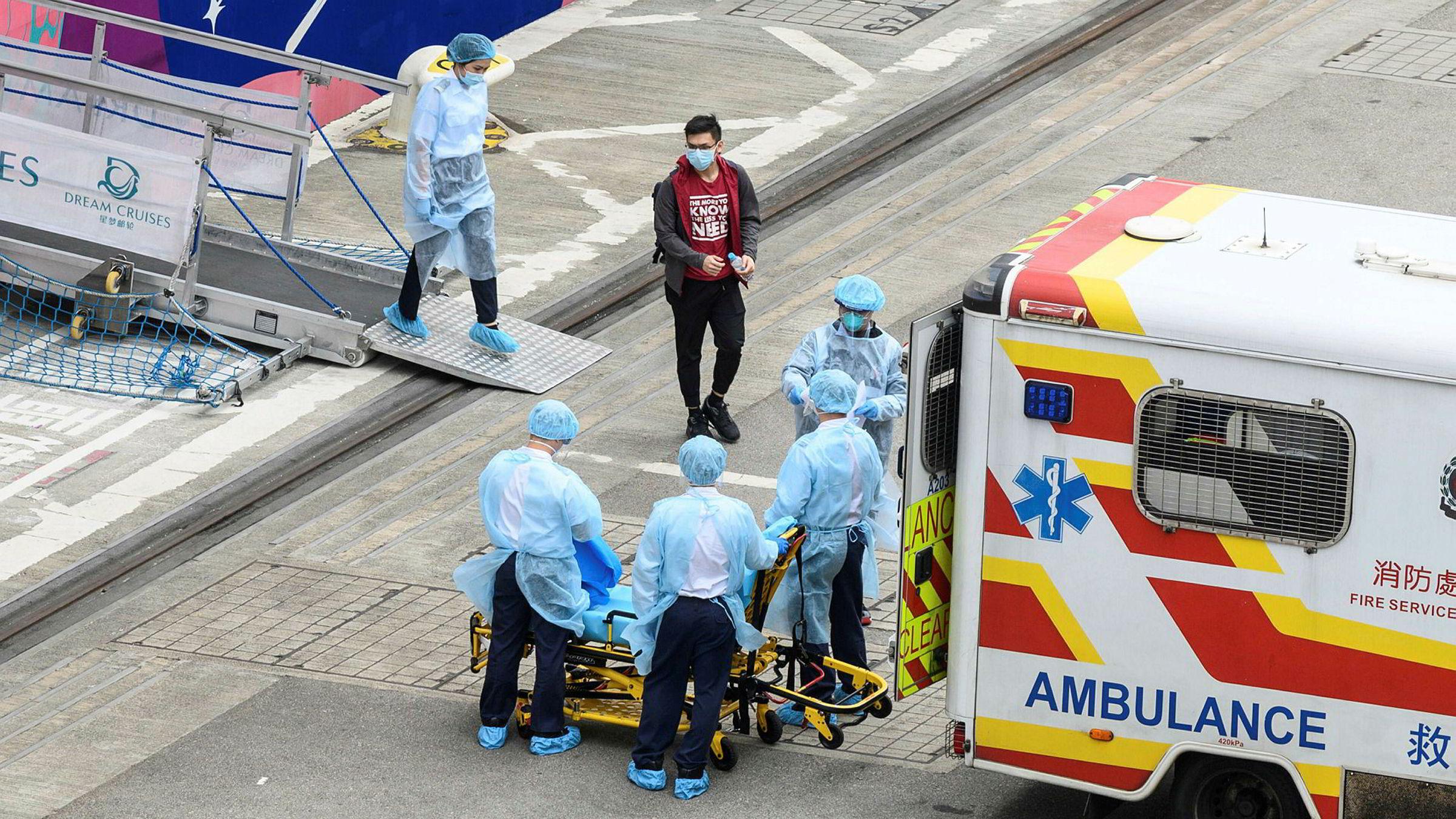 En passasjer overføres fra cruiseskipet World Dream til en ambulanse ved cruiseterminalen Kai Tak i Hongkong på onsdag. I Japan er 3700 passasjerer ombord et cruiseskip satt i karantene i 14 dager.