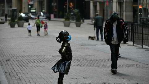 På Wall Street står bronseskulpturen «Den fryktløse piken» rett foran inngangen til New York-børsen, for anledningen med ansiktsmaske.