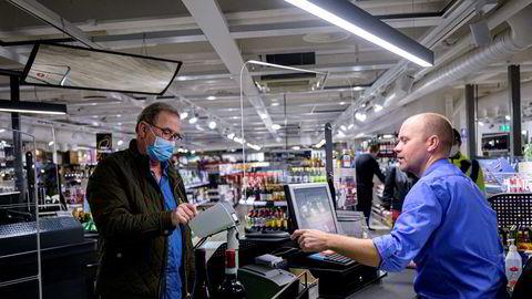Vinmonopolet er blant dem som nå opplever en ny shoppingboom. Butikksjef Jetmund Ringstad har merket at folk kjøper dyrere viner. Her ekspederer han kunde Dag Leren.