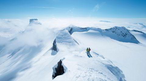 Brølende utsikt. Fra Sokse (2189 m.o.h.) ser Anne-May Slinning og Karsten -Gafle ned mot Bjørneskardet, hvor Høgruta pas-seres på turens siste dag. Til venstre ses den flate toppen på Storebjørn (2222 m.o.h.). Midt i bildet har toppen av Vesle-bjørn (2150 m.o.h.) tatt tåkehatten på.