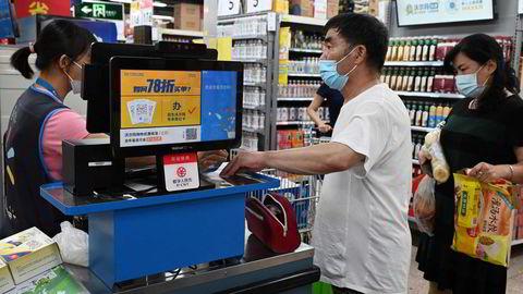 Internasjonale finansinstitusjoner har nedjustert vekstprognosene for Kina, verdens nest største økonomi, de siste uke. Det er den innenlandske etterspørselen og frykt for råtne lån i bankene som bekymrer. Her fra en Walmart-butikk i Beijing.