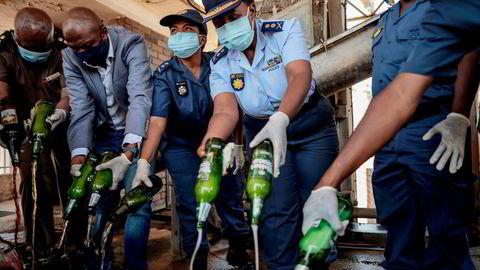 Sørafrikansk politi heller ut 2000 liter med illegal alkohol som ble konfiskert under en politioperasjon i fjor høst.