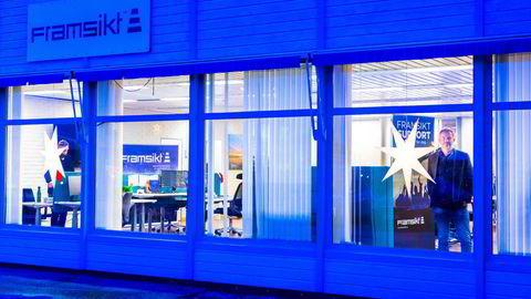 Daglig leder Halvor Walla (52) i blåtimen i vinduet hos gasellebedriften Framsikt i Bø i Vesterålen i Nordland. Framsikt holder til i et nedlagt banklokale i kommunen.