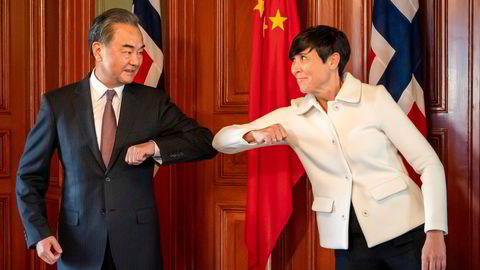 Kinas utenriksminister Wang Yi gjør en korona-hilsen med utenriksminister Ine Eriksen Søreide under en kort visitt i Norge i august i fjor.