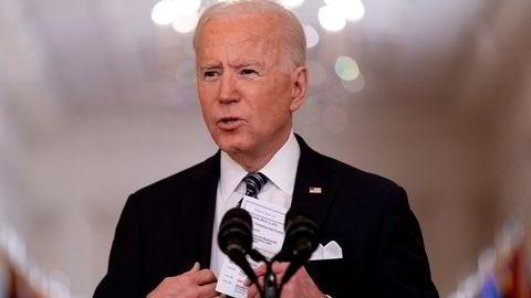 Joe Biden holder opp et kort med timeplan for dagen og med oppdaterte tall for døde av covid-19 i USA. Fredag vil Biden ha sittet 100 dager som president.
