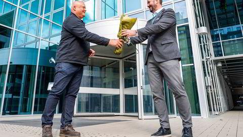 Fagdirektør i Forbrukerrådet Jorge Jensen overrekker blomster til konserndirektør i DNB Håkon Hansen for å ha opplyst om standardkompensasjon ved pensjonskonto.