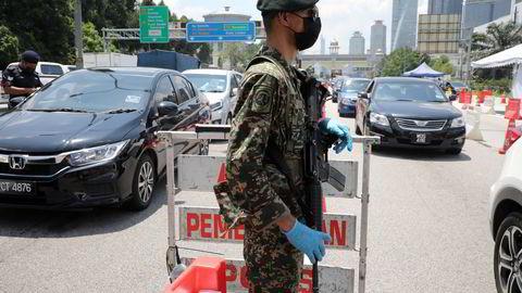 Soldater er satt inn i ved veisperringen i Malaysia i forkant av en nesten full nedstengning de neste fire ukene. Det blir forbudt å reise mellom ulike regioner og kommuner. Her fra Petaling Jaya ved hovedstaden Kuala Lumpur på mandag.