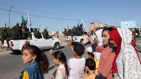 Palestinere i Gaza vinker til den væpnede delen av Hamas, Al-Qassam brigadene, under en militærparade i byen Khan Yunis torsdag.