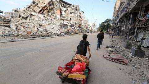 En palestinsk gutt flykter med sin bror og deres eiendeler bort fra israelske luftangrep mot Gaza by.